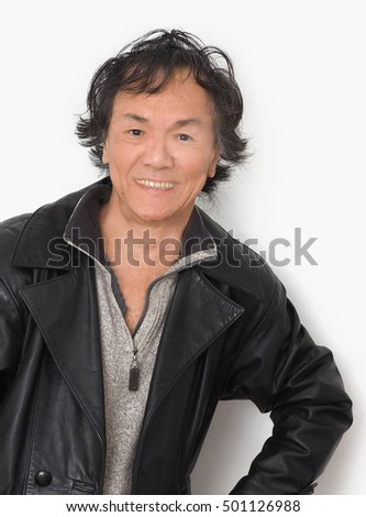 Ethic asian male black wavy coiffed hair wearing leather jacket and wool sweater.