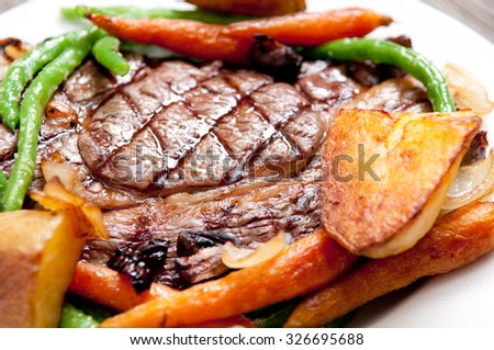 ethically raised, fresh cut organic rib eye steak grilled rare with fresh roasted vegetables - stock photo