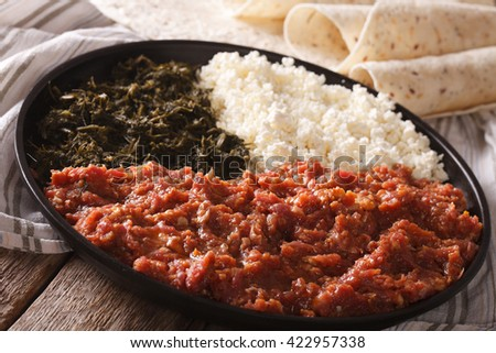 Ethiopian cuisine: kitfo with herbs and cheese on a plate and injera. Horizontal