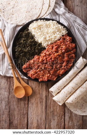 Ethiopian cuisine: kitfo with herbs and cheese on a plate and injera. vertical view from above