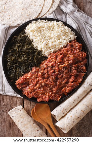Ethiopian kitfo: marinated beef with herbs and cheese close-up on a plate and injera. vertical view from above