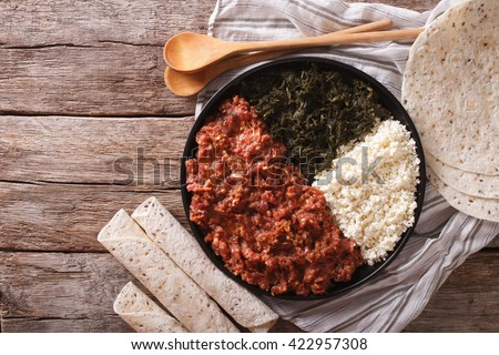 Ethiopian kitfo with herbs and cheese ayibe on a plate close-up. horizontal view from above