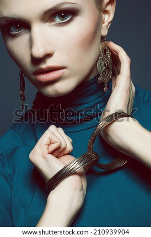 Ethnic accessories concept. Portrait of beautiful young woman in blue dress wearing golden earrings and wristbands over dark blue background. Evening make-up. Close up. Studio fashion shot - stock photo