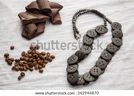 Ethnic beads, coffee beans and pieces of chocolate on a white tablecloth - stock photo
