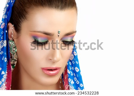 Ethnic Beauty Fashion. Beautiful hindu woman with colorful makeup, traditional clothes and jewelry. Closeup portrait isolated on white with copy space for text - stock photo