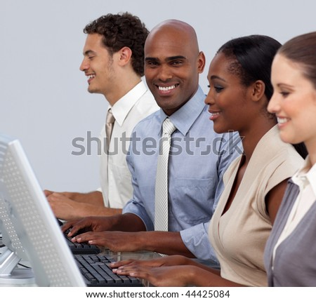 Ethnic businessman sitting in a row with his team smiling at the camera