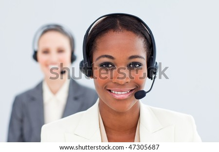 Ethnic businesswoman and her colleague with headset in a call center