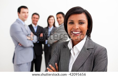 Ethnic businesswoman smiling at the camera with her colleagues in the background - stock photo