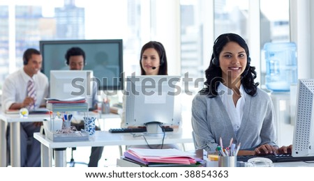 Ethnic businesswoman with a headset on in a call center - stock photo