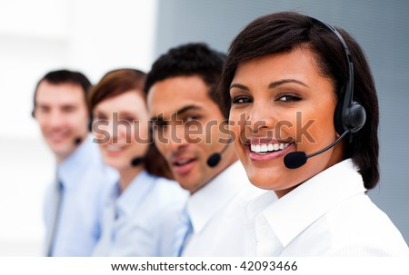 Ethnic businesswoman with headset on smiling at the camera in a call center - stock photo