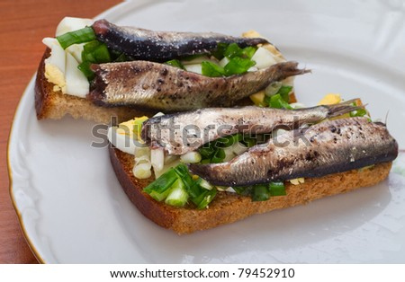 Ethnic cuisine. The Estonian national sandwich on plate. Ingredients: marinated Baltic herring, green onion, hard-boiled egg, household bread