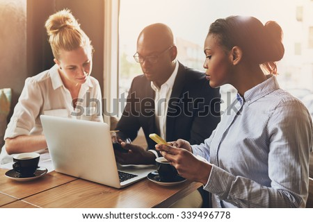 Ethnic entrepreneurs planning their work using laptop and cell phone - stock photo