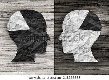 Ethnic equality concept and racial justice symbol as a black and white crumpled paper shaped as a human head on old rustic wood background with contrasting tones as a metaphor for social race issues. - stock photo