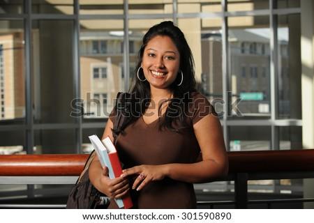 Ethnic female student inside campus building - stock photo