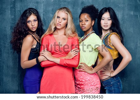 Ethnic four women face - isolated on dark wall - stock photo