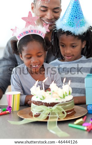 Ethnic little girl and her family celebrating her birthday in the kitchen - stock photo