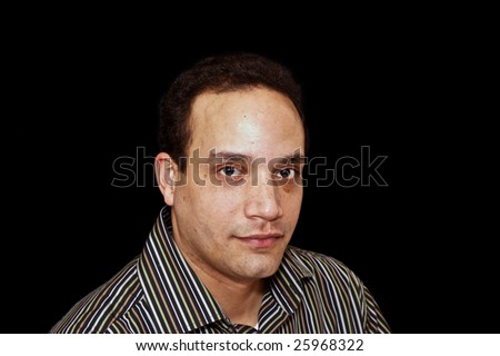 ethnic male wearing striped shirt against black background looking calm and relaxed
