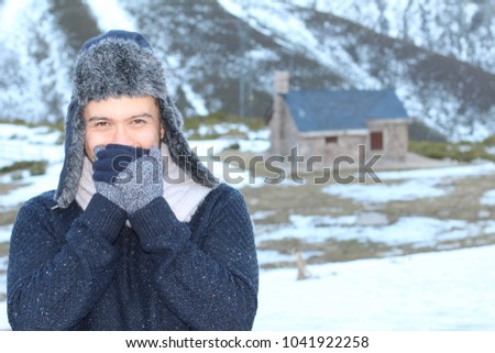 Ethnic man showing with a hand-face gesture that is freezing outside