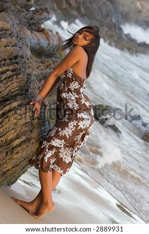 Ethnic Model leaning over rocks at the beach