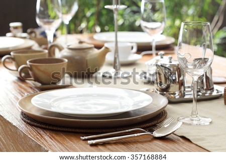 ethnic outdoor table setting on solid wood table - stock photo