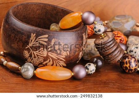 Ethnic style bracelet and necklace on wooden background - stock photo