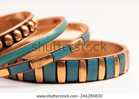 Ethnic turquoise and gold bracelets on white background - stock photo