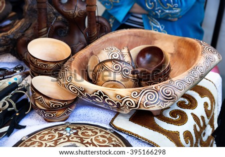 Ethnic wooden cup and bowls with oriental pattern and souvenirs in the market at Nauryz celebration in Almaty, Kazakhstan