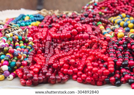 Ethnic wooden multicolored necklaces at fair, traditional decorations