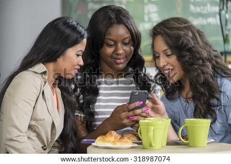 Ethnically diverse young women sharing a cellphone in a cafe - stock photo