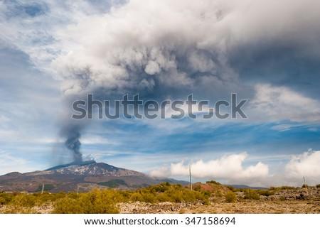 "ETNA, ITALY - DECEMBER 4 2015: Intense paroxysm (sudden eruption) on volcano Etna; ash plume emitted from the summit crater called ""Voragine"" - stock photo"