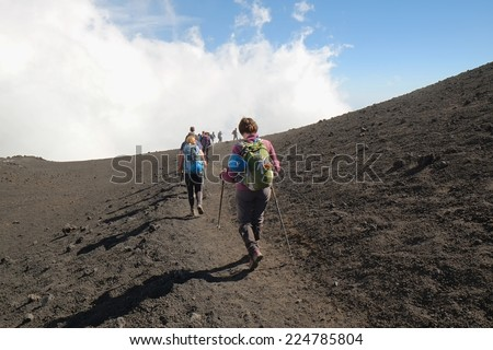 ETNA NATIONAL PARK, SICILY, ITALY - OCTOBER 18, 2014: row of hikers going down the steep path of a crater at the border with the area of high criticality of the summit south-east crater.  - stock photo