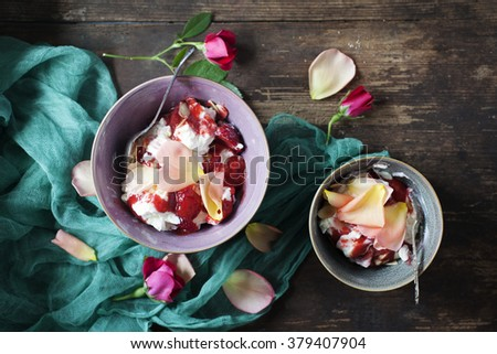 Eton Mess with strawberries and rose oil. - stock photo