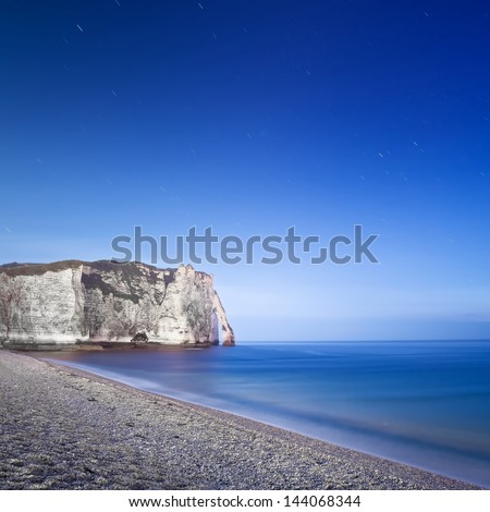 Etretat Aval cliff landmark and its beach Starring night photography. Normandy, France, Europe. Long exposure. - stock photo