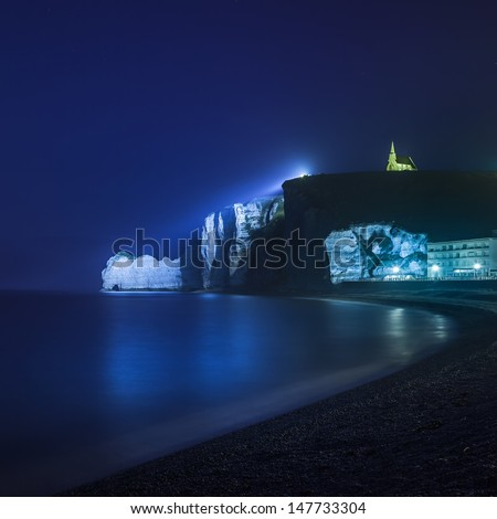 Etretat cliff and church landmark and its beach Starring night photography. Normandy, France, Europe. Long exposure. - stock photo