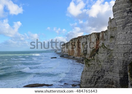 Etretat coastline cliffs during a cloudy day in Seine-Maritime department of Haute-Normandie region in north-western France.