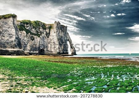 Etretat,Normandy. La Manneporte natural rock arch wonder, cliff and beach - stock photo