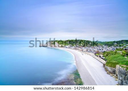 Etretat village and its bay beach, aerial view from cliff. Normandy, France, Europe. Long exposure. - stock photo