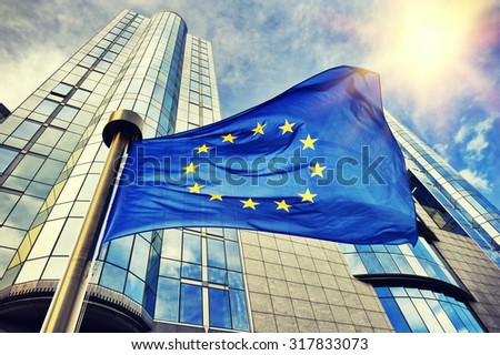 EU flag waving in front of European Parliament building. Brussels, Belgium