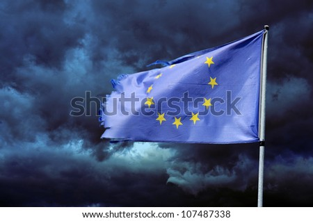 EU torn flag in stormy sky - stock photo