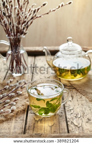 Eucalyptus tea with leaves in transparent cup and teapot on vintage wooden table background. Rustic style - stock photo