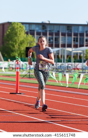 EUGENE, OR - MAY 1, 2016: Young runner on the home straightaway at the 2016 Eugene Marathon, a Boston qualifying event.