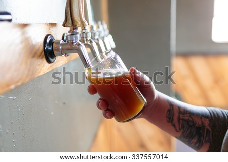 EUGENE, OR - NOVEMBER 4, 2015: Bartender and brewery co-owner Brandon Woodruff pouring Exalted IPA on tap at the startup craft brewery Mancave Brewing. - stock photo