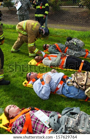 EUGENE, OREGON USA Â?Â? May 2, 2012: Eugene, OR the local Emergency Services and National Guard work together in a disaster drill. The firemen are reviewing the injury status cards on the injured. - stock photo