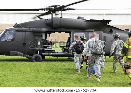 EUGENE, OREGON USA May 2, 2012: Eugene, OR the local Emergency Services and National Guard work in a disaster drill. Walking injured approach the helicopter after firemen loaded an injured person. - stock photo