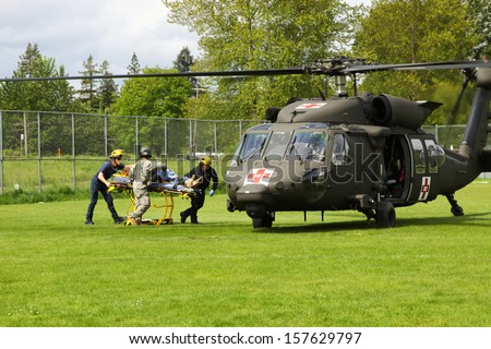 EUGENE, OREGON USA  May 2, 2012: In Eugene, OR the local Emergency Services and National Guard work in a disaster drill. The firemen carry an injured person on a gurney to the helicopter.