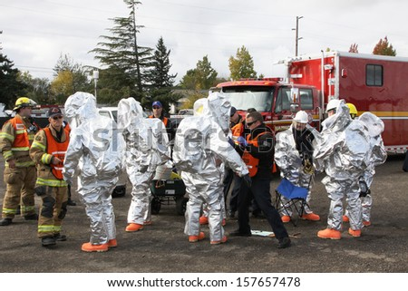 EUGENE, OREGON, USA  November 3, 2011: Eugene fire departments & emergency teams conduct disaster drills. This HAZMAT team is suiting up with PPE to protect them from hazardous materials.  - stock photo