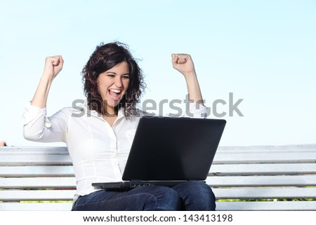 Euphoric businesswoman with a laptop sitting on a bench with the sky in the background - stock photo