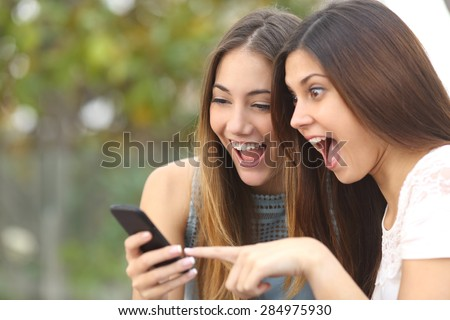 Euphoric friends watching videos on a smartphone and pointing at screen surprised - stock photo