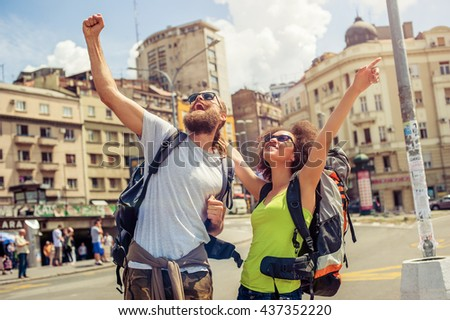 Euphoric happy couple of tourists are raising their hands up and enjoying their trip