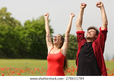 Euphoric happy couple raising arms in a country field with red flowers - stock photo